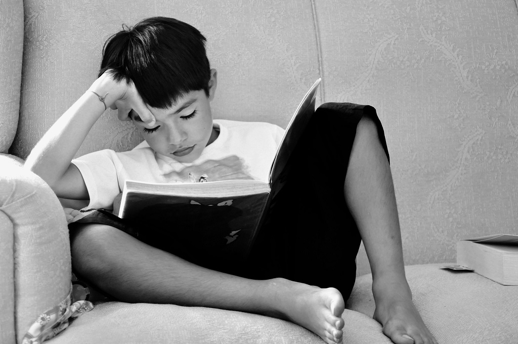 Niño leyendo un libro sólo